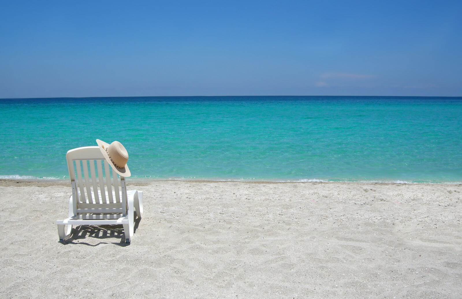 a white lounge chair with a hat resting on it on the white sand beach with clearn blue water and cloudless blue skies on a sunny day