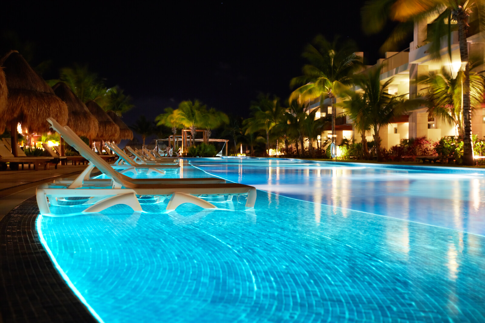 hotel with a quiet wading pool lit up in the evening with lounge chairs set up in the pool and palm frond umbrellas sitting behind the pool