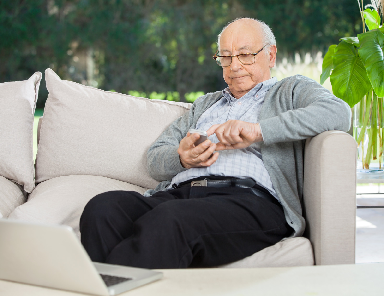 senior man sitting on a an offwhite couch texting on his smart phone