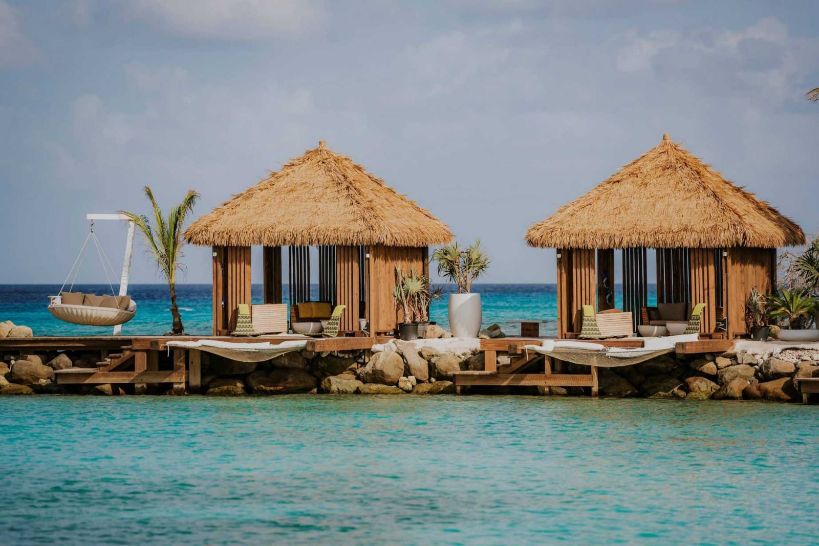 two open air Cabanas on a pier along the crystal blue waters, each furnished beautifully with relaxing sitting areas and hammocks overhanging the water