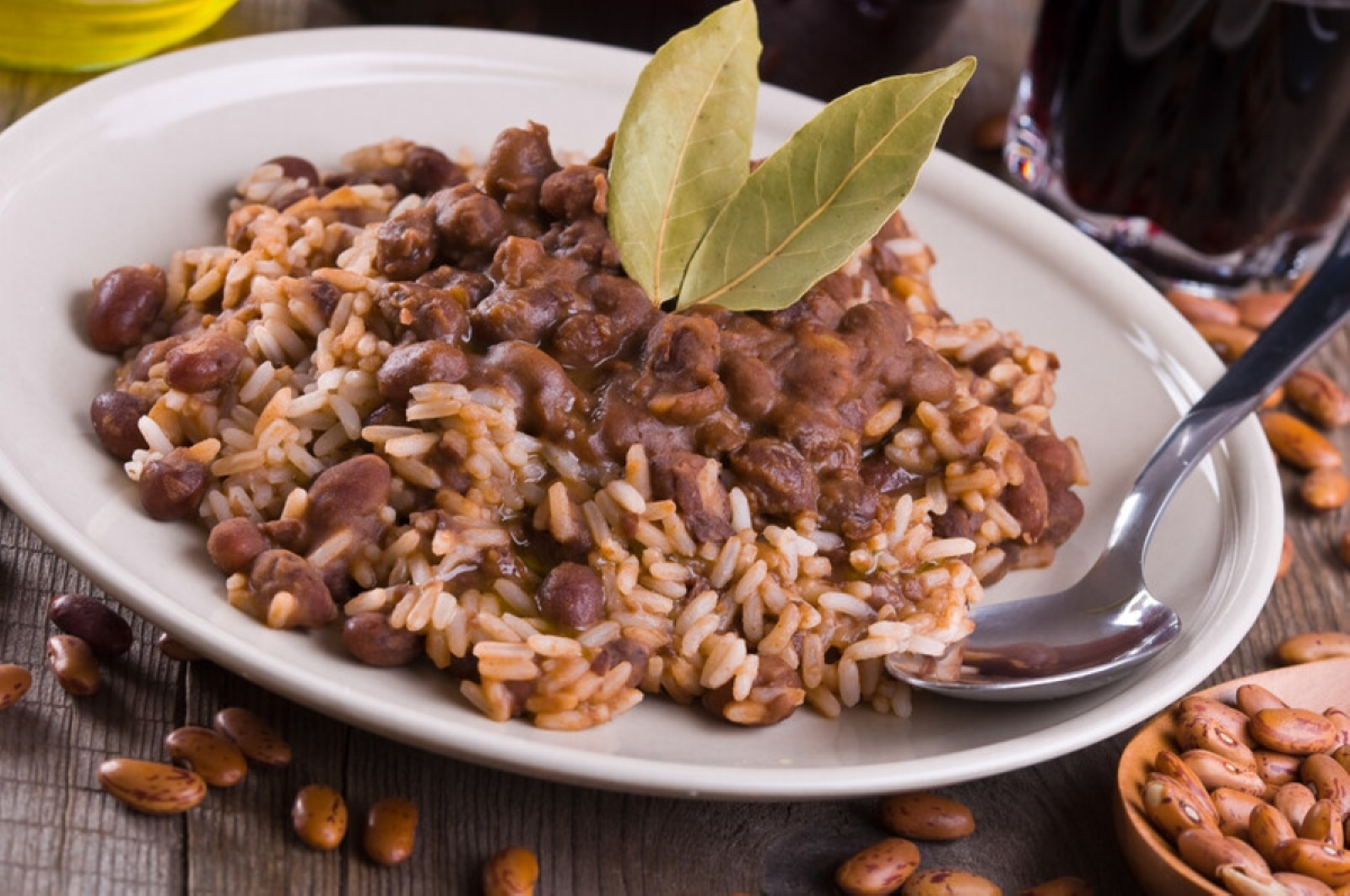 Cooked Rice and red Beans garnished with two bay leaves on a white plate with a spoon, dried beans are scattered around the plate sitting on a wood table