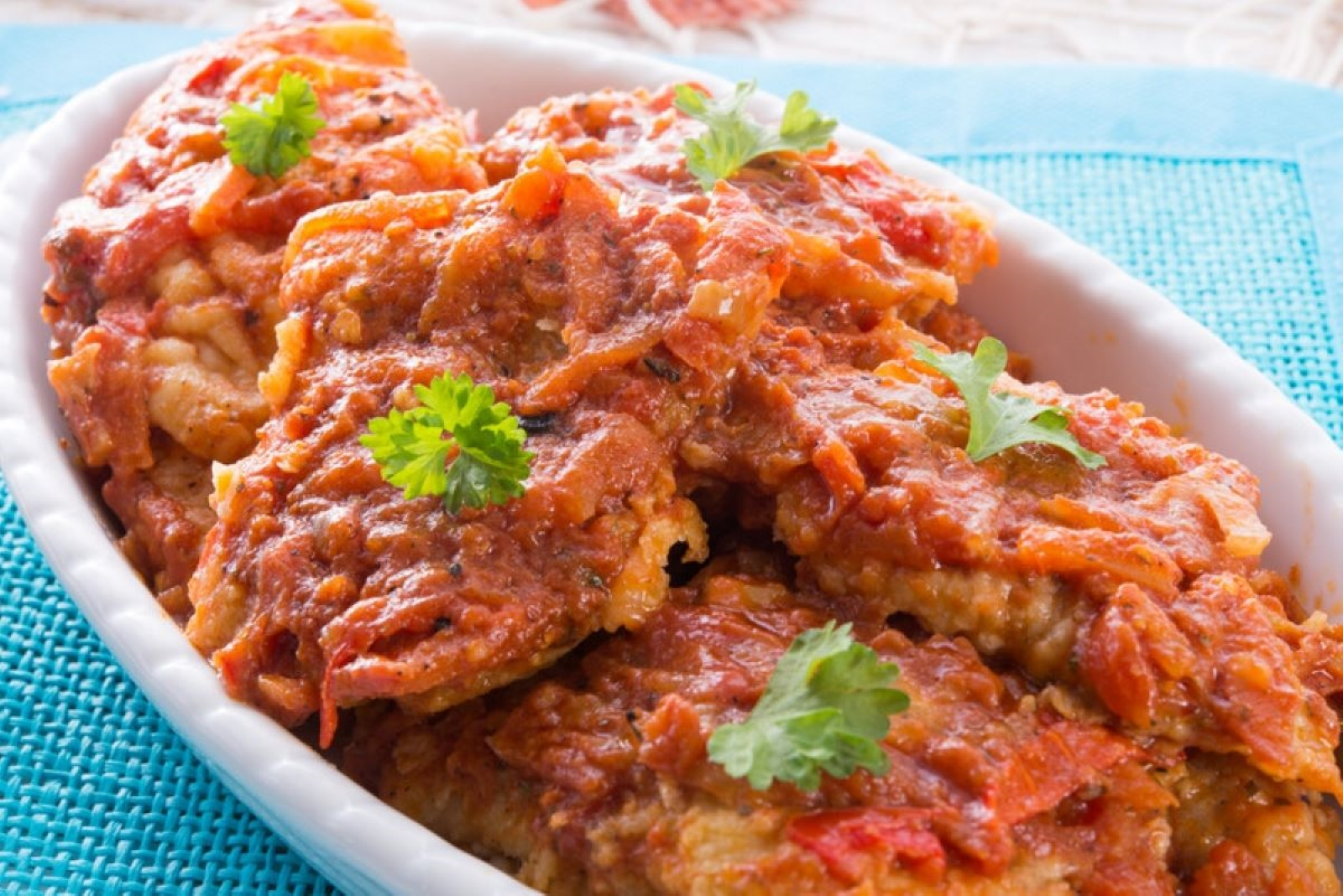 Fried fish with tomato sauce in a white oval bowl on a vibrant blue placemat