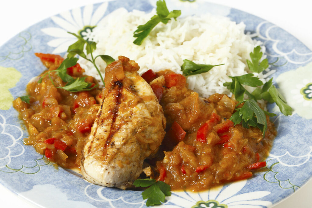 What is Caribbean food? Grilled chicken with spiced tomato and red capsicum sauce with a side of rice garnished with parsley