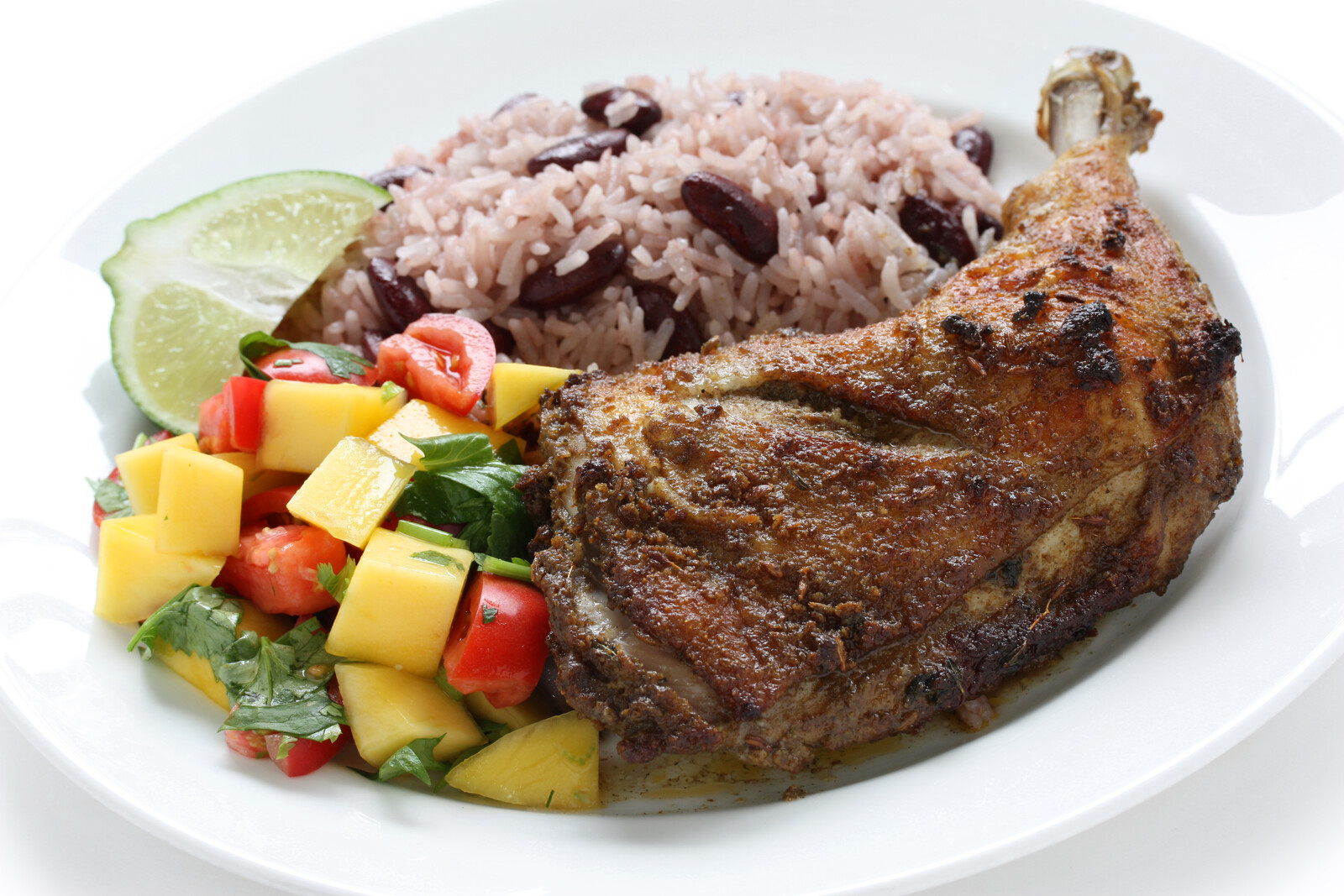Jamaican Jerk chicken with mango salsa and red beans and rice on a white plate garnished with a lime