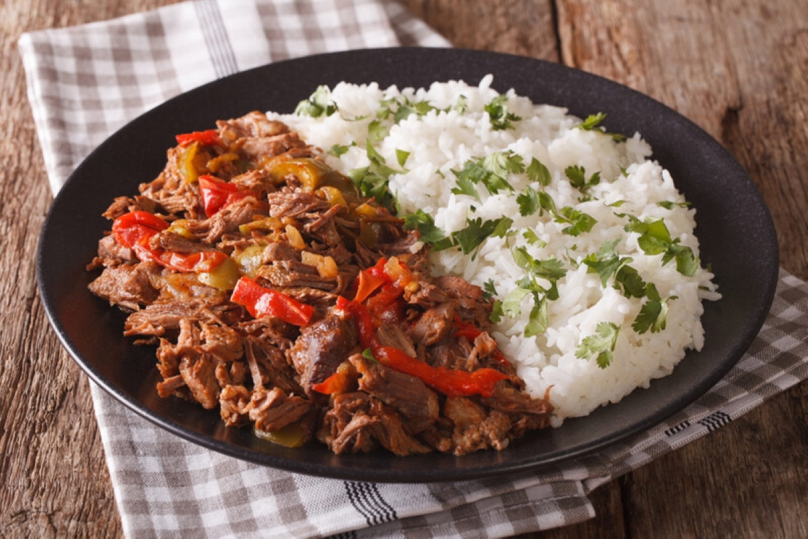 Ropa Vieja next to a bed or white rice with cilantro garnish presented on a black plate sitting on a brown plaid napkin and wooden table