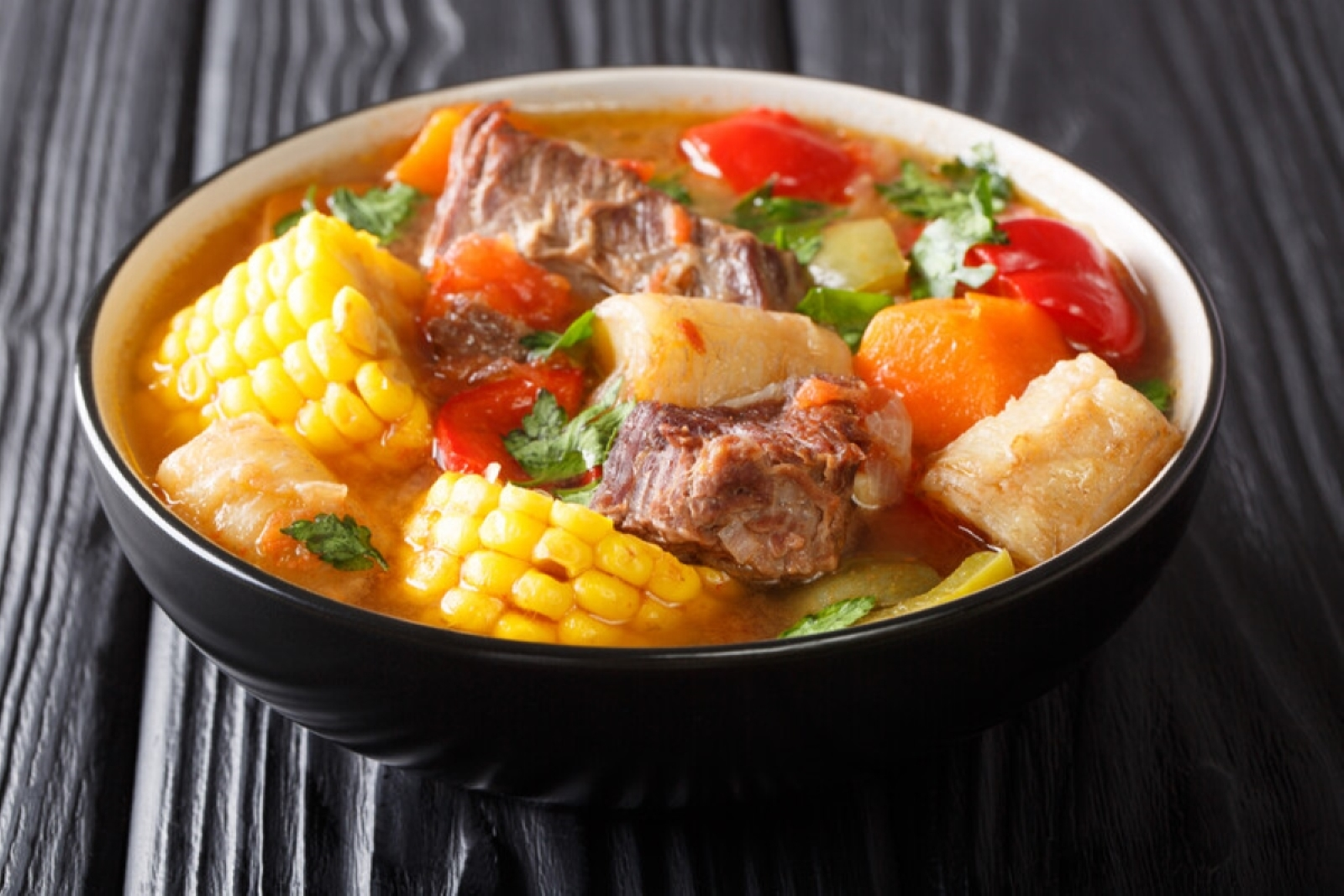 Sancocho with corn on the cob, meat, potatoes, and peppers in a black bown on a black wood table