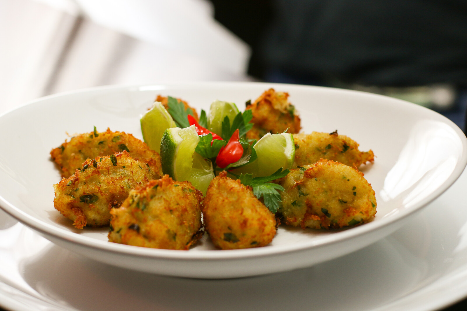 conch fritters on a white plate with limes and parsley garnishing the middle