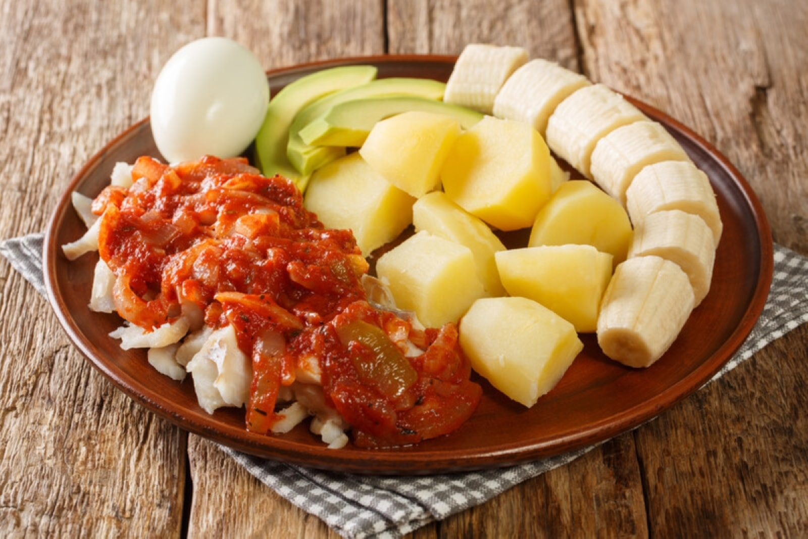 salted cod with onion tomato sauce and fresh banana, egg and avocado on a brown plate sitting on a plaid napkin on a table